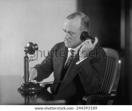 Businessman dialing an early 20th century desk phone with separate ear receiver and mouth transmitter. Ca. 1920.