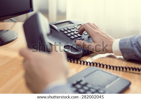 businessman dialing voip phone in the office, keyboard and monitor detail in the background with vintage color tone effect - stock photo