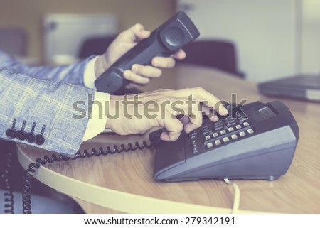 businessman dialing voip phone in vintage color effect - stock photo