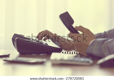 businessman dialing voip phone with pale vintage color effect - stock photo