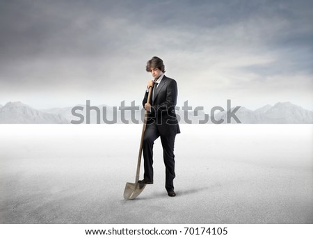 Businessman digging with a shovel in a desert - stock photo