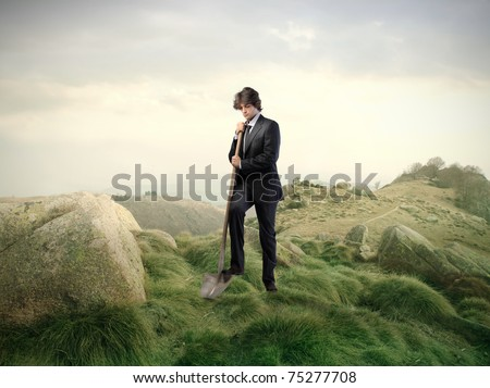 Businessman digging with a shovel in the mountains - stock photo