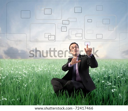Businessman digitizing on a touchscreen on a green meadow - stock photo