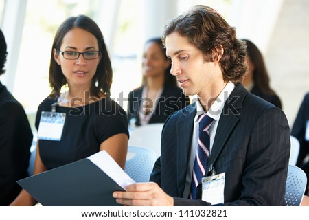 Businessman Discussing Conference Document With Colleague - stock photo