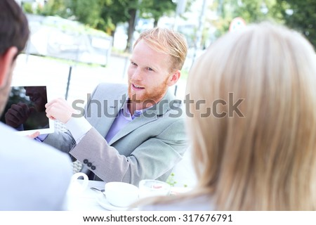 Businessman discussing over digital tablet with colleagues at sidewalk cafe - stock photo