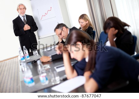 Businessman discussing sales targets at a meeting with his inattentive and sleepy team - stock photo
