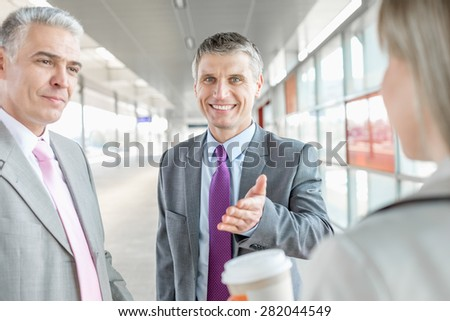 Businessman discussing with colleagues at railroad platform - stock photo