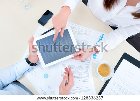 Businessman discussing with financial analyst business development strategy project and using modern digital tablet with chart on a screen. Top view photo shoot.