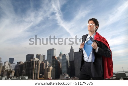 Businessman disguised in superman with cityscape on the background - stock photo