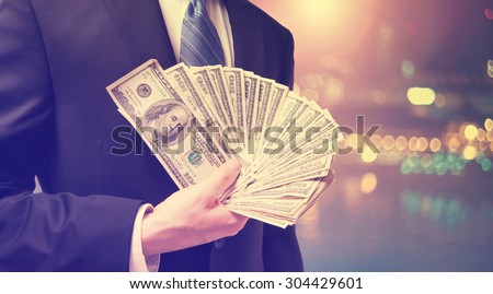 Businessman displaying spread of cash on blurred city background  - stock photo