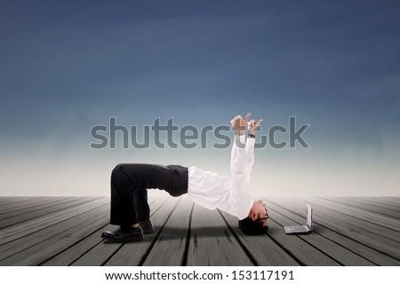 Businessman doing bridge yoga over blue sky background - stock photo
