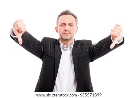 Businessman doing double thumb down gesture looking serious on white background