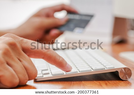 Businessman doing online banking, online shopping, making a payment or purchasing goods on the internet entering his credit card details on a pc, close up view of his hands. - stock photo