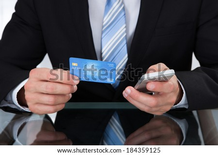 Businessman doing online banking or making a purchase through an online store using his dank credit card  and a mobile phone close up view of his hands - stock photo