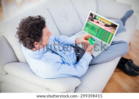 Businessman doing online shopping on couch against gambling app screen - stock photo