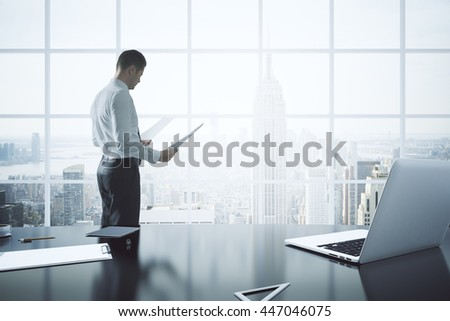 Businessman doing paperwork in office with laptop, clipboard and other items on desktop. Window with New York city view in the background. 3D Rendering