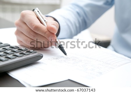 Businessman doing some paperwork in his office - stock photo