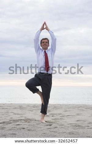 Businessman doing yoga on a beach - stock photo