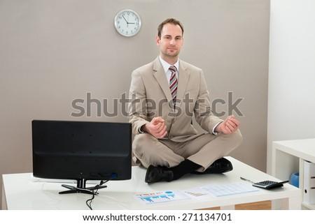 Businessman Doing Yoga On Desk In Office - stock photo