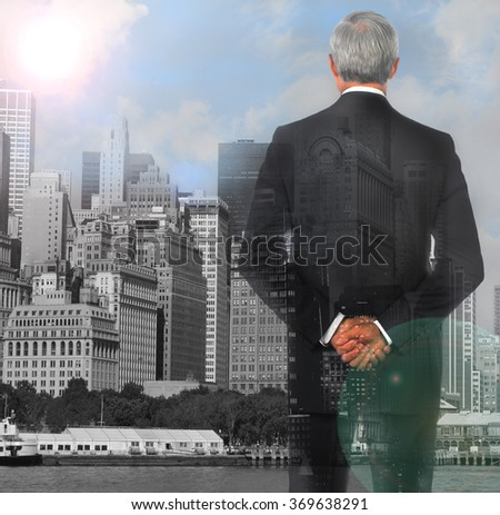 Businessman double exposure with his hands clasped behind his back with city background and lens flare. - stock photo