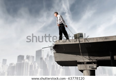Businessman dragging a computer monitor on a bridge