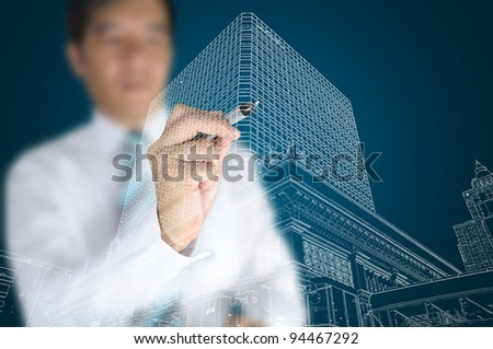Businessman draw modern building and cityscape - stock photo