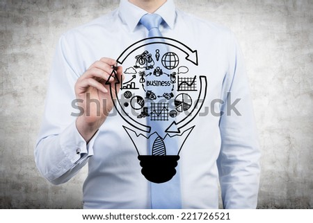 Businessman drawing a business idea. Lightbulb and a business cycle flowchart.  - stock photo