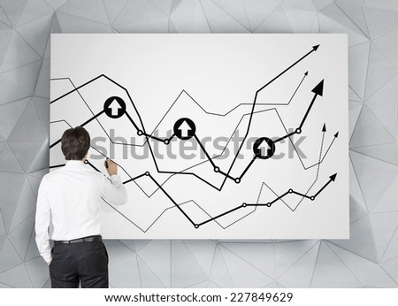 Businessman drawing a chart on the whiteboard.  - stock photo