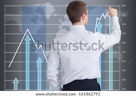 Businessman drawing a graph on a big touchscreen showing the success of the company - stock photo