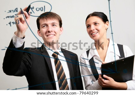 Businessman drawing a graph on a glass window in an office - stock photo