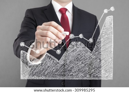 Businessman drawing a graph with chalk - stock photo