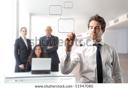 Businessman drawing a graphic with group of business people on the background - stock photo