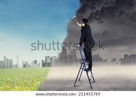 Businessman drawing a green city from a city with air pollution - stock photo