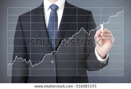 Businessman drawing a growing chart with chalk  - stock photo