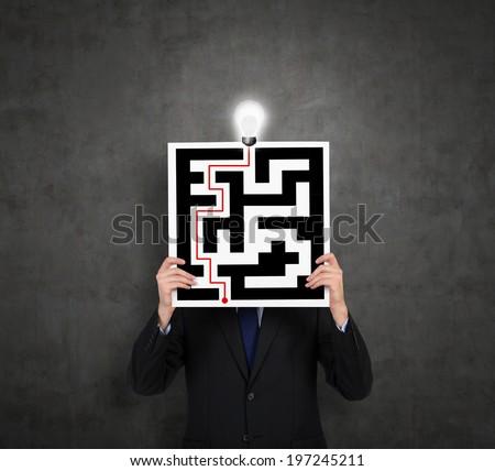 Businessman drawing a labyrinth  - stock photo