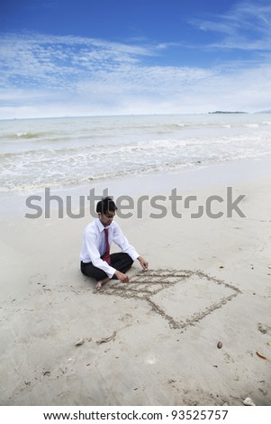 Businessman drawing a laptop on the sand
