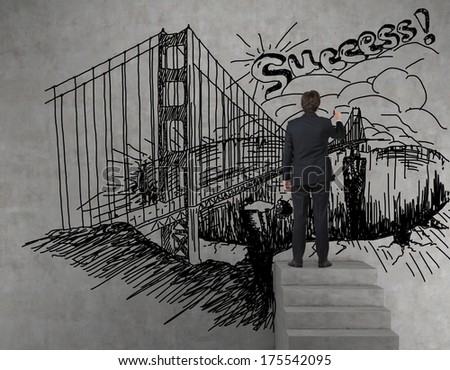 Businessman drawing a picture of success in a wall  - stock photo