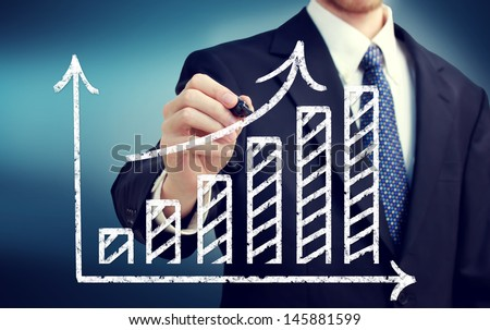 Businessman drawing a rising arrow over a bar graph - stock photo