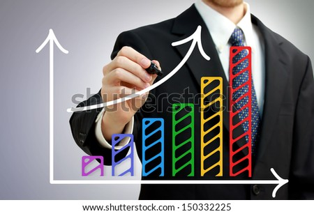 Businessman drawing a rising arrow over a colorful bar graph - stock photo