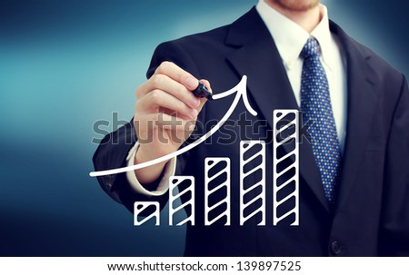 Businessman drawing a rising arrow over the bar graph - stock photo