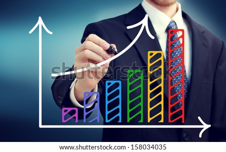 Businessman drawing a rising arrow over the colorful bar graph - stock photo