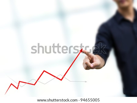 Businessman drawing a rising arrow, representing business growth. - stock photo