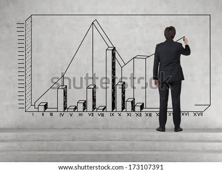 Businessman drawing an economic graph - stock photo