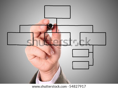businessman drawing an organization chart on a gray background - stock photo