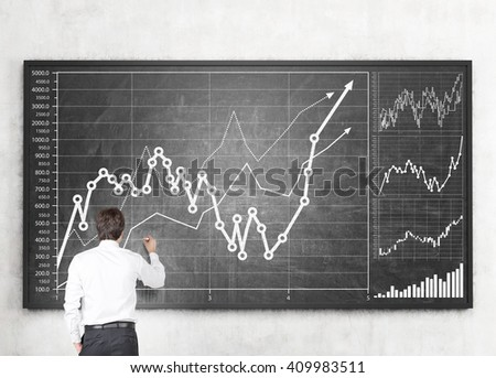 Businessman drawing business graph on blackboard - stock photo