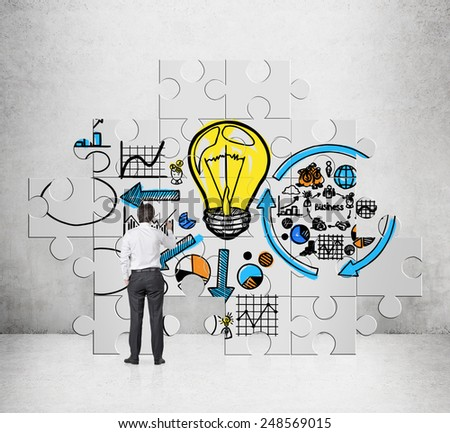 businessman drawing business startegy on puzzle