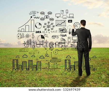 businessman drawing business strategy on field background - stock photo