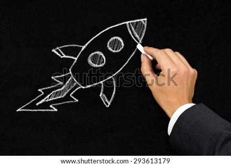 Businessman drawing cartoon rocket with chalk on blackboard background - innovation, startup or idea concept - stock photo