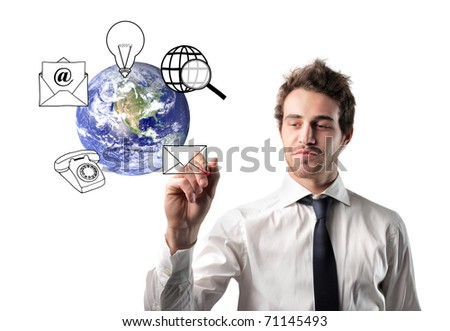 Businessman drawing communication symbols around the earth - stock photo