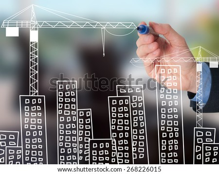 Businessman drawing construction site project ( building development ). Business man draw crane and cityscape. Isolated on office. Stock Image - stock photo